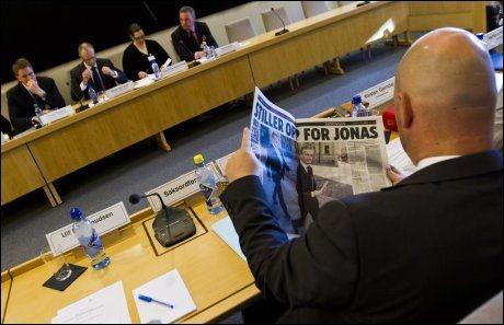 GRILLET JONAS: Komitéleder Anders Anundsen (FrP), med ryggen til, leser en artikkel om utenriksminister Jonas Gahr Støre før den åpne høringen i Stortingets kontroll- og konstitusjonskomité. Foto: Vegard Grøtt / NTB scanpix
