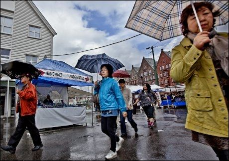 SOM FISKEN I VANNET: Regnet pøste ned da disse japanske turistene besøkte Bergen i juli 2010. Foto: GEIR OLSEN / VG