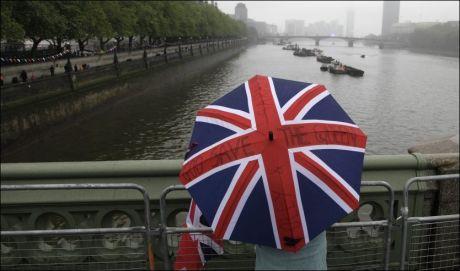 TÅLMODIG: En tilskuer har sikret seg god plassering til båtoppvisningen med dronning Elizabeth søndag ettermiddag. Foto: REUTERS