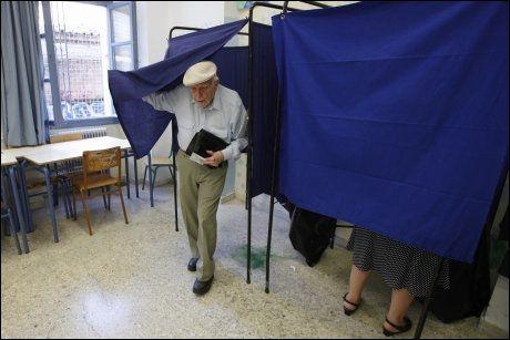 TIL VALGURNENE: En eldre gresk mann avgir sin stemme ved et stemmelokale i Athen tidiligere i dag. Nå telles stemmene mens verden holder pusten. Foto: Reuters