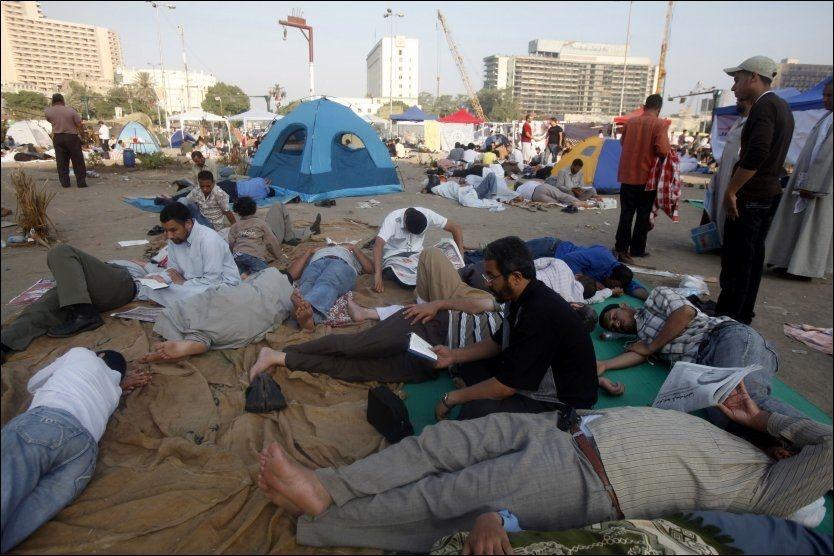 En demonstrant leser koranen mens andre slapper av på Tahrir-plassen i Egypts hovedstad Kairo. Egypterne må fortsatt vente på resultatet av presidentvalget, og ventingen utløser uro som kan føre til nye store protestdemonstrasjoner, sa politiske observatører torsdag. Foto: Asmaa Waguih