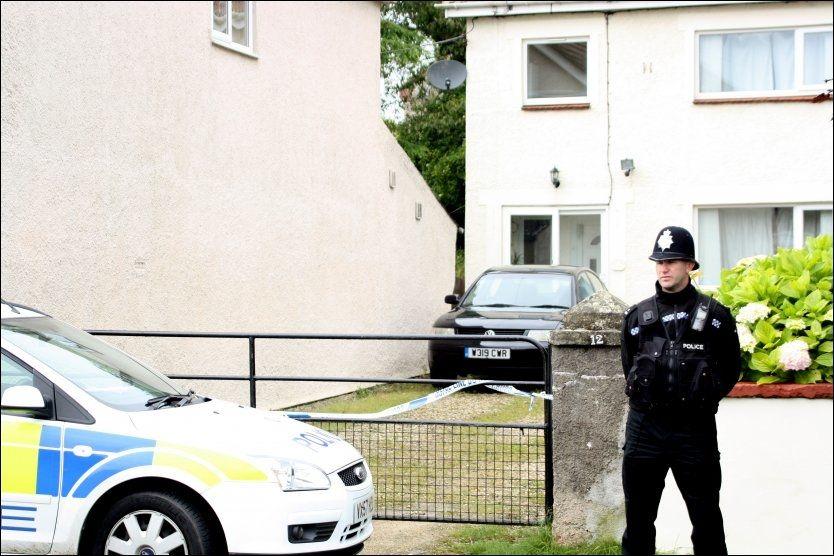OPPRØRT: En politimann vokter huset hvor familien Fuller bodde. Flere naboer har gått forbi huset, oppløst i tårer. Foto: Pa Photos