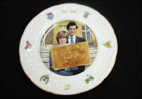 BLE IKKE SPIST: Et stykke ristet brød ligger vakkert dandert på en tallerken med bilde av den britiske tronarvingen prins Charles og hans avdøde kone Diana. Foto: Hanson's Auctioneers / Reuters / NTB scanpix