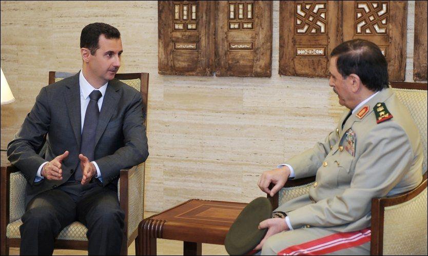 VILLIG TIL Å GÅ AV: Syrias president Bashar al-Assad skal ifølge Russlands ambassadør i Paris ha gått med på en plan hvor han trer av. Her i samtale torsdag med sin nyutnevnte forsvarsminister. Foto: AP / Bulgarias Innenriksdepartement