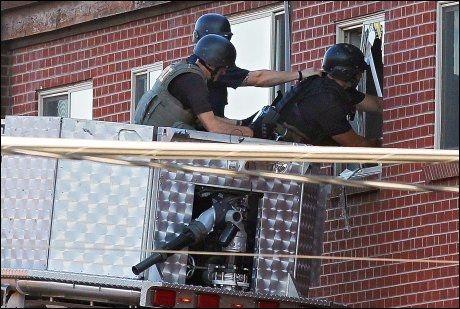 UNDERSØKER LEILIGHET: Amerikansk politi er her på vei inn i leiligheten til den mistenkte 24-åringen i Aurora i Colorado. Inne i leiligheten skal politiet ha funnet kjemikalier og ammunisjon. FOTO: Ap