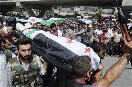 DREPT: En død person svøpt i det syriske flagget bæres til graven etter å ha blitt drept i kampene i Aleppo fredag. Foto: Alberto Prieto, AP / NTB Scanpix