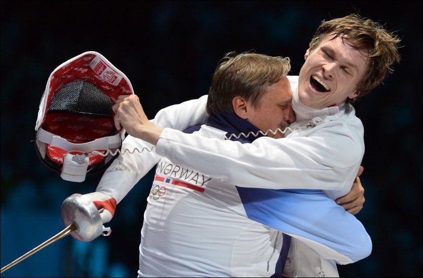 SMEKTENDE FEKTENDE: Bartosz Piasecki får en god jubelklem av pappa og trener Mariusz etter semifinalen. Foto: AFP