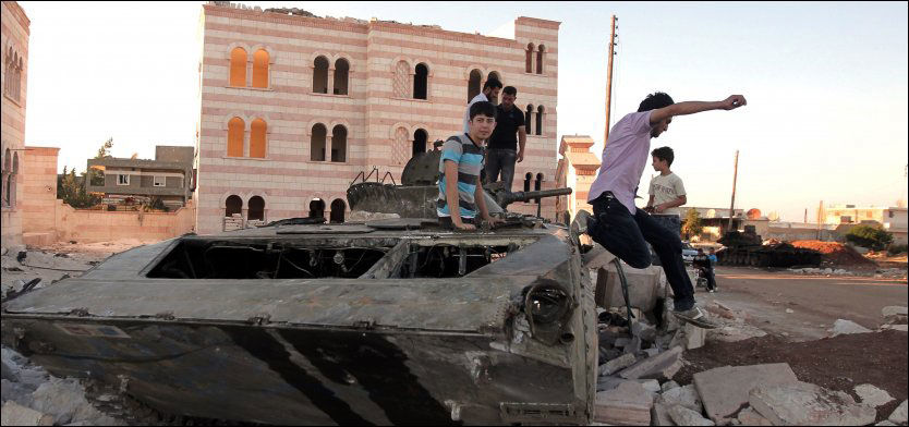 FN UT HERFRA: Sikkerhetsrådet fornyer trolig ikke FN-observatørenes rolle i Syria. Det sier Frankrikes FN-ambassadør i dag. Bildet viser syrisk ungdom som leker foran en ødelagt syrisk stridsvogn i Aleppo torsdag Foto: AFP