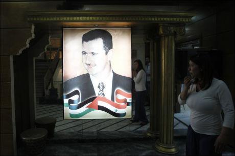 PRESIDENTPORTRETT: Et portrett av Syrias president Bashar al-Assad henger i TV- og radiobygget i Damaskus. Tirsdag møter Assad den iranske rådgiveren Saeed Jalili i den syriske hovedstaden. Foto: Khaled al-Hariri / Reuters / NTB scanpix