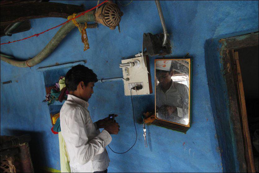 MED MOBIL: En gutt lader mobiltelefonen sin med strøm fra et solcellepanel i familiens hus i landsbyen Meerwada, i den sentrale delstaten Madhya Pradesh. Da landsbyen fikk tilgang til solcellepaneler i fjor forandret livet i byen seg. Foto: Adnan Abidi / Reuters / NTB scanpix