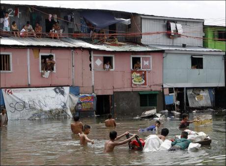 PÅ HUSTAKENE: Innbyggere på Filippinene klatrer opp på hustakene sine i et forsøk på å komme unna vannmassene. Foto: Erik De Castro/Reuters