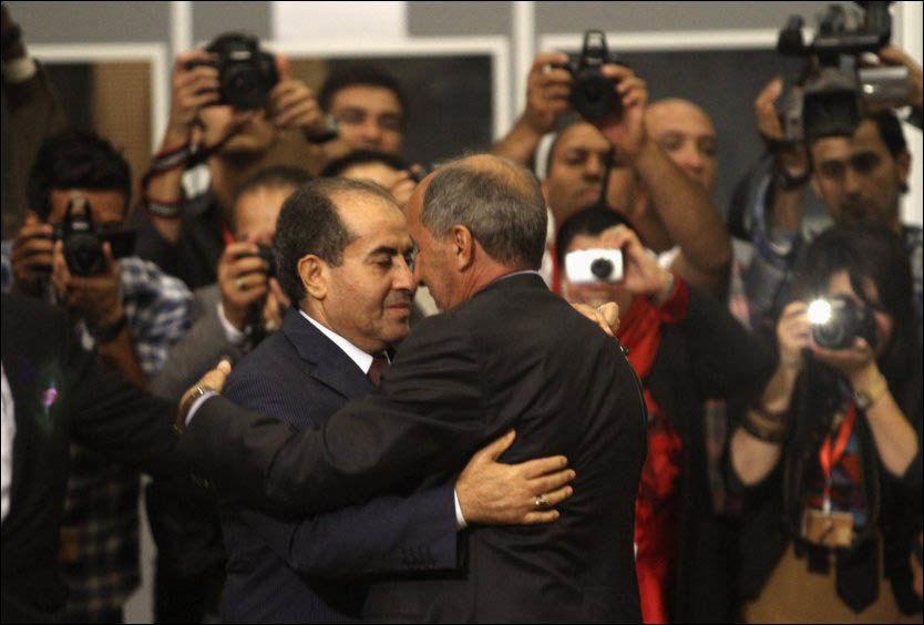 FREDELIG: Overgangsrådets leder Mustafa Abdel Jalil (t.h.) omfavner Mahmoud Jibril, som var statsminister i Libya under borgerkrigen, under seremonien i Tripoli onsdag kveld. Foto: Reuters / NTB scanpix