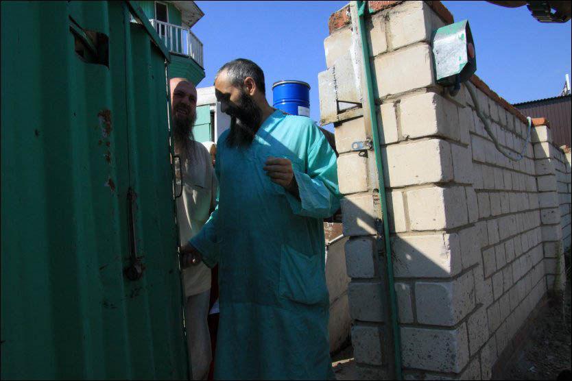 BODDE UNDER BAKKEN: To av medlemmene i den muslimske sekten i Russland står her utenfor et hus i Karzan. Nesten 70 medlemmer skal ha levd i en underjordisk bunker i ti år. Foto: Nikolay Alexandrov / AP