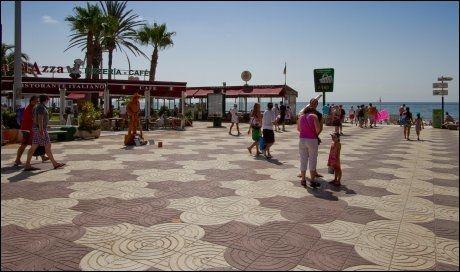 USPENNENDE: Strandpromenaden i Playa del Ingles er velkjent for de mange nordmenn. Men i området vrimler det også av trash-selgere, timeshire-pushere og ikke minst promotører med skraplodd som prøver å få naive turister på feriepakke-kroken. Nå skal det ryddes opp. Foto: Båd Ove Myhr