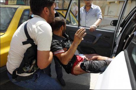 SKADET: En skade mann bæres ut av en bil fra Alepppo av en opprører. Foto: Reuters