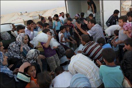STRØMMER TIL JORDAN: Et stort antall mennesker har flyktet fra borgerkrigen i Syria til Jordan. Her venter syriske flyktninger på is i en flyktningeleir i Mafraq i Jordan. Foto: REUTERS