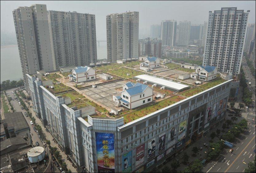 VIL HA VILLA: Slike hus er sjelden kost i Kina, men i denne byen har man funnet en helt ny måte å få plass til både hus og hage på. Foto: EPA/BO WAY CHINA OUT