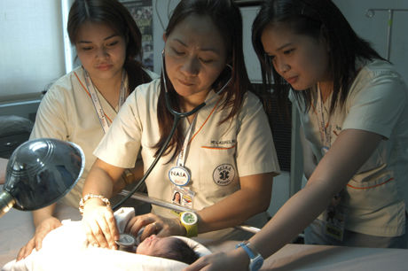 ADOPTERT BORT: Sosialarbeidere på Filippinene undersøker en baby som ble forlatt på et fly i 2010. Filippinene har i dag flere utenlandske søkere som ønsker et barn, enn de har barn å gi bort. Foto: Ap Photo/NTB Scanpix