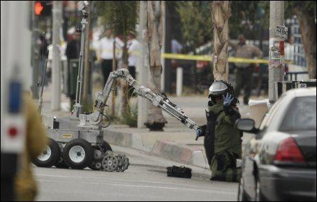 FAREN OVER: En person fra bombepatruljen signaliserer at faren er over, etter å ha undersøkt et det bankdirektøren trodde var eksplosiver. Foto: DAMIAN DOVARANES