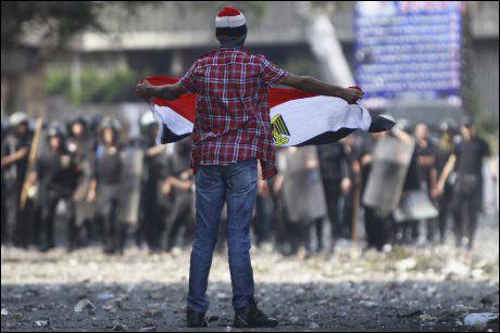 PROTESTERER: EN demonstrant roper slagord mens han vifter med et egyptisk flagg framfor politiet utenfor den amerikanske ambassaden i Kairo. Foto: REUTERS
