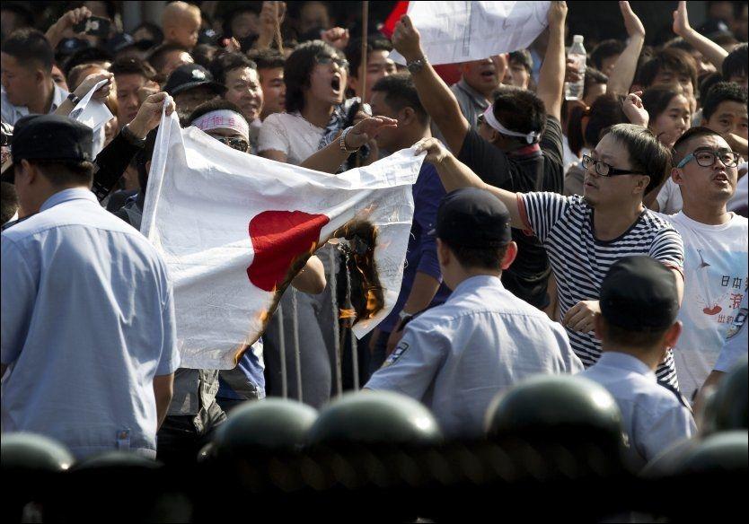 OPPHETET: Kinesiske demonstranter brenner et Japansk flagg under en protest utenfor den Japanske ambassaden i Beijing, lørdag 15. september. FOTO: Andy Wong, Ap/NTB/Scanpix