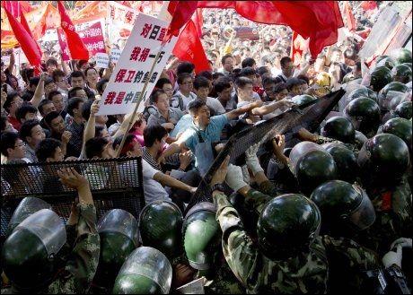 OPPTØYER: Kinesiske demonstranter møter store politistyrker under en anti-Japansk protest i Beijing i helgen. FOTO: Andy Wong, Ap/NTB/Scanpix