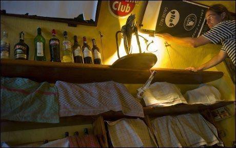 GJEMMES BORT: En bartender dekker hyllene som inneholder flasker med brennevin. Verken barer, resultanter eller butikker får lov å selge det etter at Tsjekkia innførte totalforbud. Foto: AFP