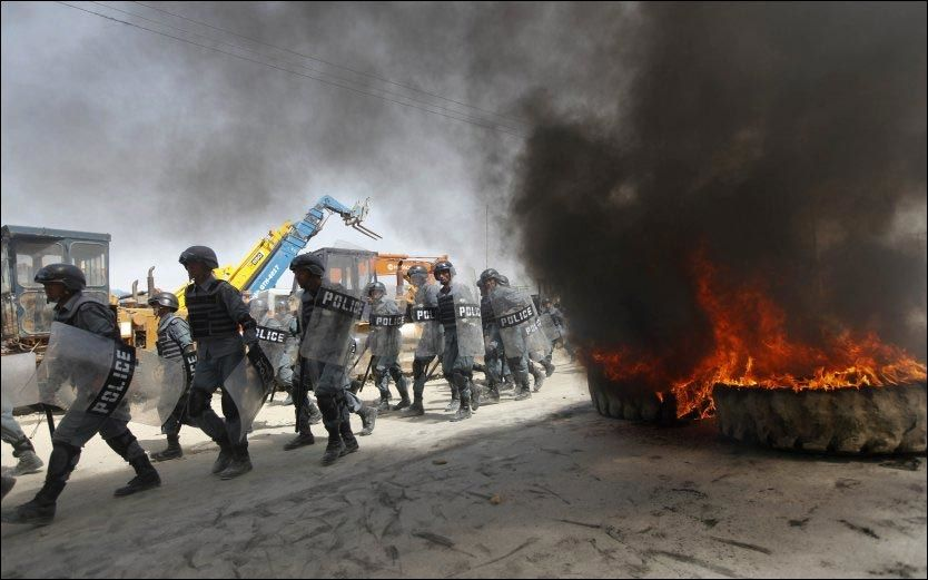 STORE DEMONSTRASJONER: Afghanske politimenn marsjerer mot demonstranter under en demonstrasjon i Kabul mandag. Tusenvis hadde tatt til gatene for å protestere mot Muhammed-filmen. Foto: REUTERS