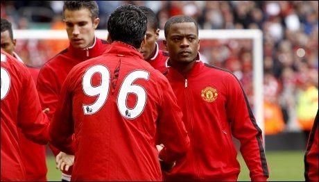 SLUTT PÅ BRÅKET: Luis Suarez og Patrice Evra viste at de har lagt bråket mellom dem bak seg, da de tok hverandre i hendene før avspark på Anfield søndag. Foto: Pa Photos