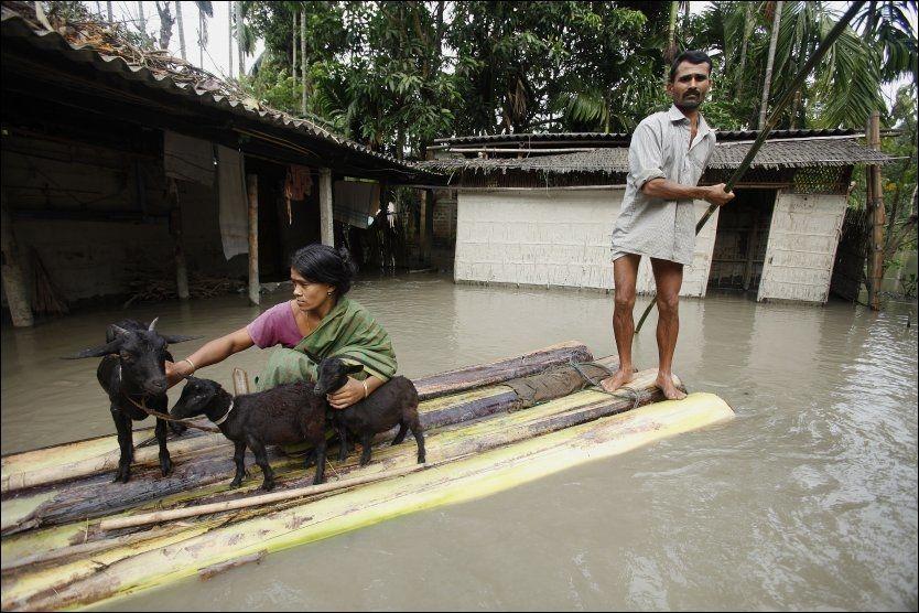 EVAKUERER: 27 mennesker har mistet livet i flommen som rammer den nordøstlige delen av India. Her forlater et ektepar hjemmet sitt i delstaten Assam. Foto: AP