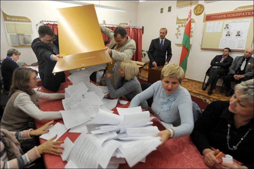 TELLER OPP: Medlemmer av en av valgkommisjonene i Minsk i Hviterussland teller stemmesedler etter valget søndag. Myndighetene oppga at deltakelsen var på 74,3 prosent i valget, til tross for mange indikasjoner på et langt lavere oppmøte. Foto: AFP