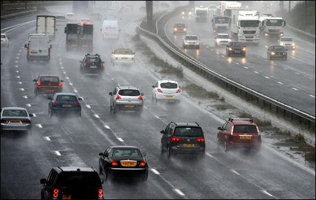 VANSKELIGE KJØREFORHOLD: Den kraftige vinden og nedbøren skal ha ført til flere alvorlige trafikkulykker. Her hovedveien M6 i Nord-England. Foto: AFP
