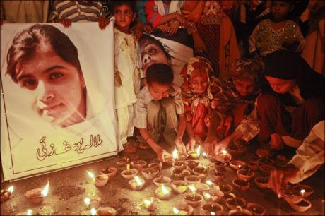 TENNER LYS: Pakistanske barn tenner lys for Malala Yousufzai (på plakaten), som ble skutt i hodet og forsøkt drept av islamske ekstremister fordi hun oppfordret til utdanning for jenter og advarte mot den fundamentalistiske gruppen Taliban. Foto: Athar Hussain / Reuters