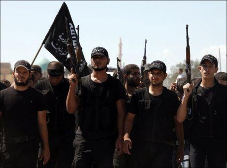KJEMPER HELLIG KRIG: Islamistiske krigere med svarte flagg under en begravelse i Aleppo i Syria, et av områdene opprørerne står sterkt. Foto: REUTERS