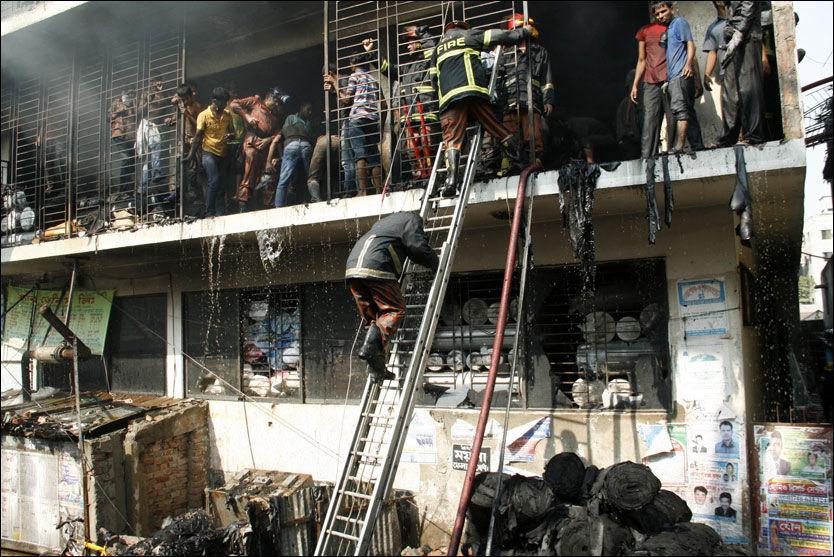 BRANNER: To dager etter lørdagens brann, som kostet minst 110 mennesker livet, brant det på ny på mandag. Her jobber brannvesenet med å få kontroll på brannen. Det er ikke registrert noen drepte etter mandagens brann. Foto: AP