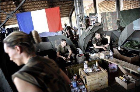 En avdeling med franske marinesoldater slår leir i gamle hangarer ved den militære delen av Senou Internasjonale flyplass i hovedstaden Bamako i Mali. Om noen dager skal de videre nordover for å kjempe mot islamistene som har tatt kontroll over store deler av Nord-Mali. Også franske jagerfly og heliokoptre er stasjonert ved den samme basen. Det er også noen få kvinner blant marinesoldatene. Det franske flagget kommer fort på plass, det er svært populært blant de lokale innbyggerne i hovedstaden akkurat nå. Foto: Harald Henden.