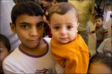 FØDT INN I KRISE: Åtte måneder gamle Hammat bor i idrettshallen sammen med familien sin. Han ble født inn i konflikten, og har aldri opplevd noe annet. Foto: Mari A. Mørtvedt/Norges Røde Kors