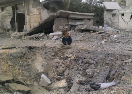 BARN I KRIG: En liten syrisk gutt sitter ved et krater som opposisjonelle sier er resultatet av en bombe som det syriske regimet har sluppet over al-Yadoudeh-området i Deraa sør i Syria. Bildet ble tatt 30. mars. Torsdag kom det meldinger om nye angrep mot andre byer i området. Foto: Reuters / NTB scanpix