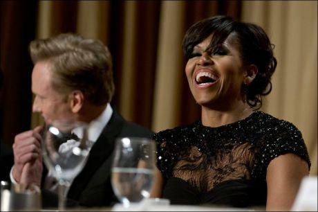 HUMOR: Førstefrue Michelle Obama lo godt under mannens grilling av pressen. Hun skal ha ledd minst like godt da han selv ble grillet. I bakgrunnen sees kveldens vert, komiker Conan O`Brien. Foto: AP Photo/Carolyn Kaster