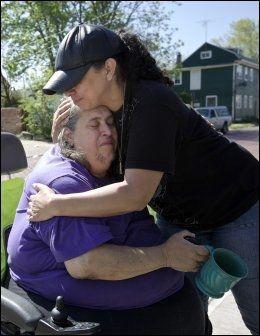 STØTTE: Naboen Sandra Guisao klemmer Michelle Knights bestemor Deborah. Foto: REUTERS/John Gress