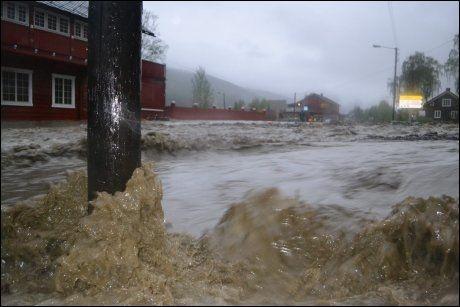 FANGET: Kvam sentrum var onsdag kveld oversvømmet av vann fra elevene Storeåa og Vesleåa. Bildet ble tatt like før kl. 22. Foto: Henning Kamp