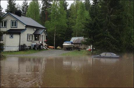 MER ENN NOEN GANG FØR: Vannstanden rundt huset har nådd mellom 60 og 70 centimeter. Ved huset står en bil som har vann opp til panseret. Foto: TOR-ERLING THØMT RUUD
