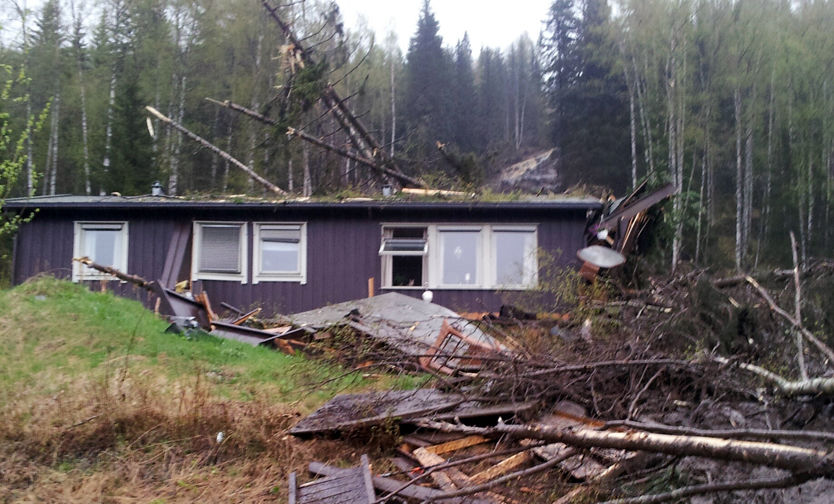 SPIDDET: Flere store tømmerstokker har gått rett gjennom huset som prosjektil, og deler av bygningen samt verandaen forsvant anslagsvis flere hundre meter nedover heien. Foto: PRIVAT