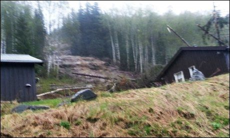 RASET: Et ti meter bredt og anslagsvis 500-600 meter langt ras tok med seg deler av huset til Rognås og Kjørli. Tømmerstokker spiddet tak og vegger. Nabohuset til høyre (ikke i dette bildet) ble fylt med jord. Foto: PRIVAT