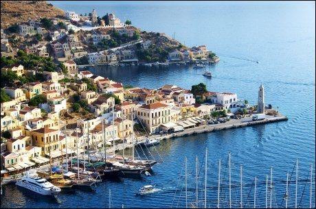 SYMI: Øya er også kjent for de pastellfargete husene. Foto: APOLLO