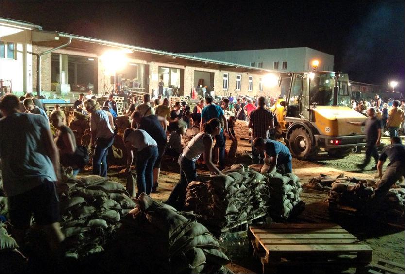 BESKYTTER MAGDEBURG: Hundrevis av frivillige er i natt samlet for å fylle sandsekker i Magdeburg. Byen står i fare for å bli totalt oversvømt i natt. Foto: THOMAS GRABKA