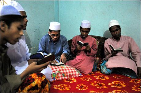 BØNN: En gruppe elever fra en koranskole i området har kommet på besøk til familiens enkle ettroms bopel i forstaden Savar, utenfor hovedstaden Dhaka. De messer koranvers samtidig som de vugger frem og tilbake. De ber for hans avdøde hustru og for at redningsarbeiderne skal finne kroppen hennes, slik at hun kan begraves på skikkelig vis. Foto: STIAN EISENTRÄGER