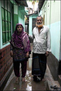 LÅ FASTKLEMT: Nupur Begum (25) og hennes far Shah Alam Talukder fotografert utenfor hjemmet deres i Savar, en forstad til Dhaka. Hun og broren var på jobb som vanlig i sjette etasje i Rana Plaza den dagen høyhuset kollapset. Selv ble hun sittende fast i ruinene i to og en halv time før redningsarbeidere greide å få armen hennes løs, mens broren fortsatt er savnet. Den studentdrevne hjelpeorganisasjonen Community Action skal nå bistå faren å åpne en liten butikk, siden familien nå har mistet hovedinntektskilden sin. Foto: STIAN EISENTRÄGER