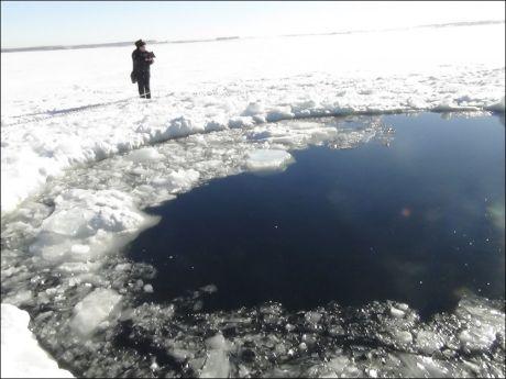 KRATER: En politimann ved det gapende hullet i isen meteoritten i Russland etterlot seg. Foto: Reuters