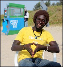 ÅPNER SEG: «Lion Man» jobber som innkaster på en strandrestaurant i Gambia, og forteller i VGTVs dokumentar om kvinnelig sexturisme om hvordan eldre kvinner betaler for sex med unge menn. I bakgrunnen selger kompisen Aladdin ferskpresset juice fra sin lille kiosk. Foto: Roar Dalmo Moltubak